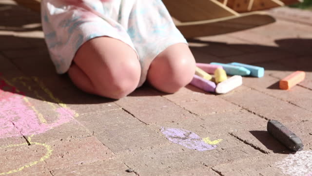 ms shot of young girl drawing on ground with chalk / lamy, new mexico, united states - gessetto da lavagna video stock e b–roll