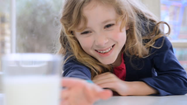 CU Shot of young girl drinking glass of milk and smiling / London, Greater London, United Kingdom