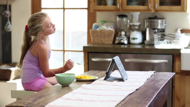 MS PAN Shot of young girl eating and watching her tablet in her kitchen / Lamy, New Mexico, United States