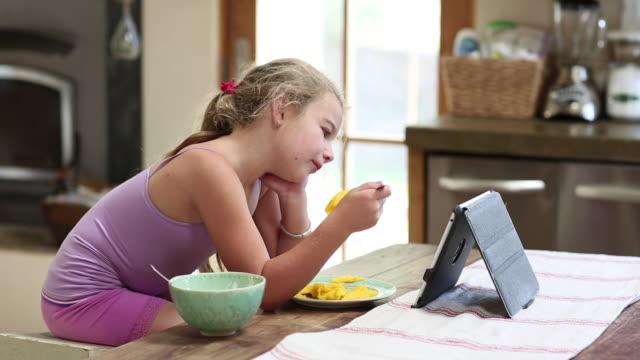 MS Shot of young girl eating and watching her tablet in her kitchen / Lamy, New Mexico, United States