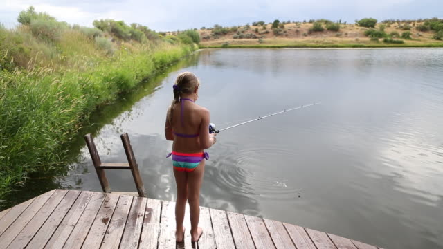 ms shot of young girl fishing in lake / st. simon's island, georgia, united states  - nur mädchen stock-videos und b-roll-filmmaterial