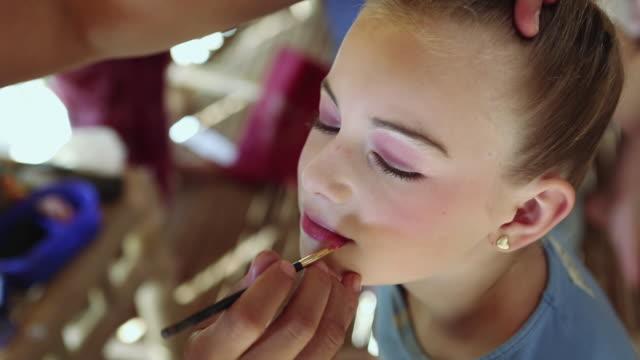 vídeos de stock, filmes e b-roll de cu shot of young girl getting her makeup applied / ubud, bali, indonesia - batom rosa