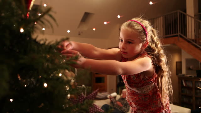 ms shot of young girl hanging christmas ornaments on tree / lamy, new mexico, united states - lamy new mexico stock videos and b-roll footage