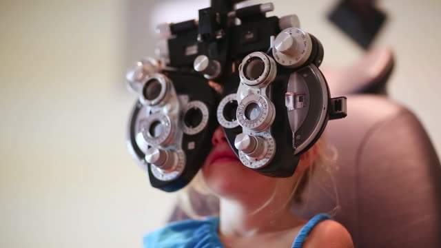 cu r/f shot of young girl having eye exam / lamy, new mexico, united states - lamy new mexico stock videos and b-roll footage
