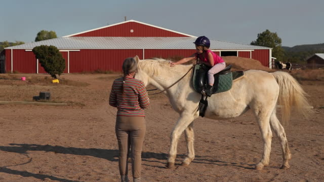 ms shot of young girl having horseback riding lesson / lamy, new mexico, united states - lamy new mexico stock videos and b-roll footage