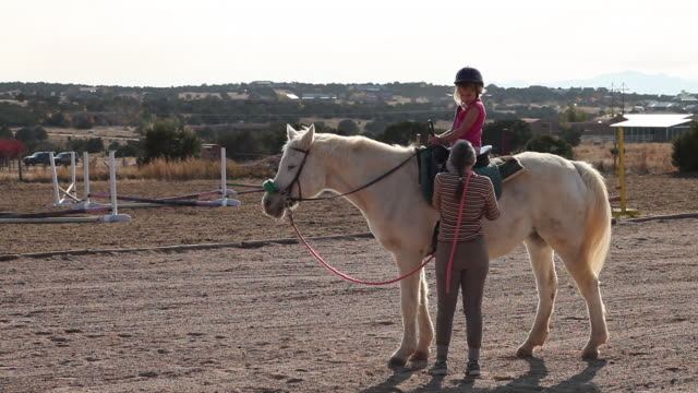 MS Shot of young girl having horseback riding lesson / Lamy, New Mexico, United States