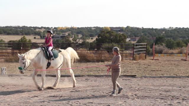 ms shot of young girl having horseback riding lesson / lamy, new mexico, united states - 働く動物点の映像素材/bロール