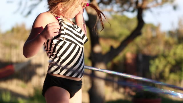 MS TU TD Shot of young girl hula hooping near pool / Lamy, New Mexico, United States