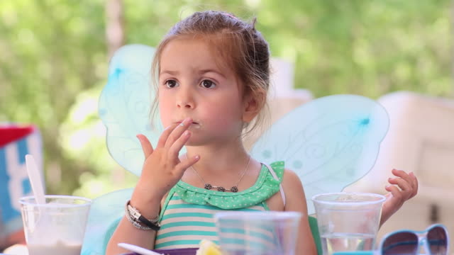 ms shot of young girl in fairy wings eating birthday cake / st simon's island, georgia, united states - disposable cup stock videos and b-roll footage