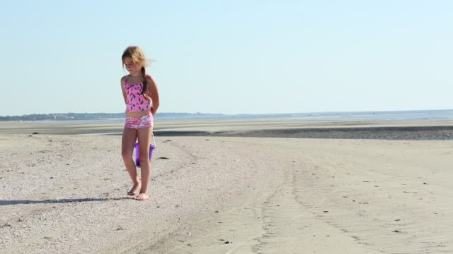 WS Shot of young girl looking for shells at beach / St Simon's Island, Georgia, United States