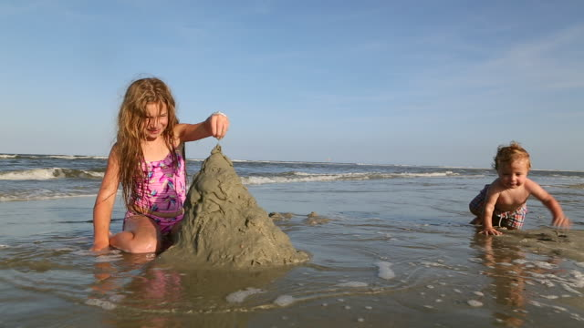 MS Shot of young girl making sand castle with baby brother / St Simon's Island, Georgia, United States
