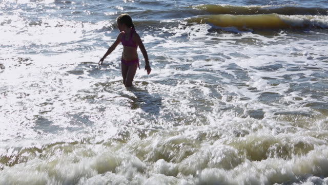 MS Shot of young girl playing and swimming in waves / St. Simons Island, Georgia, United States
