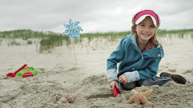 ms shot of young girl playing happily in sand at beach / st. peter ording, schleswig holstein, germany  - digging stock-videos und b-roll-filmmaterial