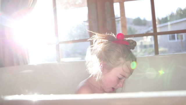 ms pan shot of young girl playing in bath tub / lamy, new mexico, united states - bathroom stock videos & royalty-free footage