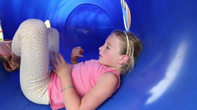ms pan shot of young girl playing in blue tunnel at playground / lamy, new mexico, united states - lamy new mexico stock videos and b-roll footage