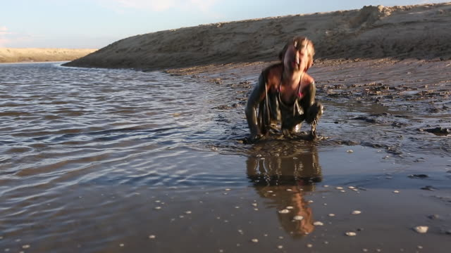 MS Shot of young girl playing in muddy water / St. Simons Island, Georgia, United States