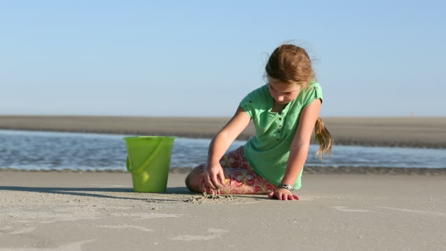 ms shot of young girl playing on beach pouring sand to bucket / st simon's island, georgia, united states - bangle stock videos & royalty-free footage