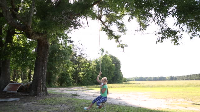 ws td shot of young girl playing on rope swing / st simon's island, georgia, united states - rope swing stock videos & royalty-free footage