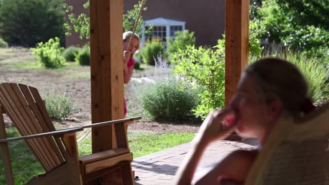 vídeos y material grabado en eventos de stock de ms shot of young girl playing on swing on her porch / lamy, new mexico, united states - sentado