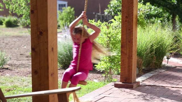 MS PAN Shot of young girl playing on swing on her porch / Lamy, New Mexico, United States