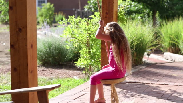 MS TD Shot of young girl playing on swing on her porch / Lamy, New Mexico, United States