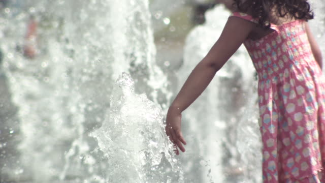 MS SLO MO Shot of young girl playing with fountain of water