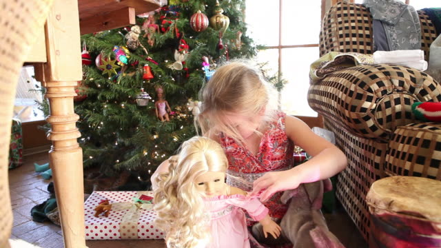 ms shot of young girl playing with her new doll on christmas / lamy, new mexico, united states - lamy new mexico stock videos and b-roll footage