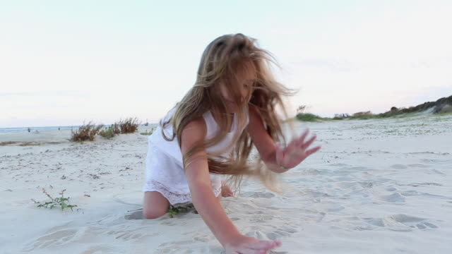 MS Shot of young girl playing with sand at beach / St. Simons Island, Georgia, United States