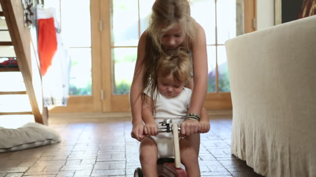 vidéos et rushes de ms shot of young girl pushing her baby brother on his ride on toy / st simon's island, georgia, united states - soeur