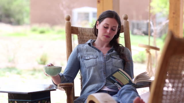 MS Shot of young girl reading on her porch / Lamy, New Mexico, United States