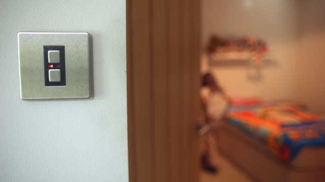 MS R/F Shot of Young girl running and jumping into bed with Light switch in foreground