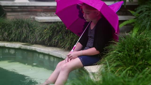 MS TD Shot of young girl sitting in rain with umbrella on edge of pool / Ubud, Bali, Indonesia
