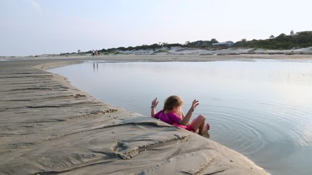 ms shot of young girl sitting in water at beach / st simon's island, georgia, united states - endast flickor bildbanksvideor och videomaterial från bakom kulisserna