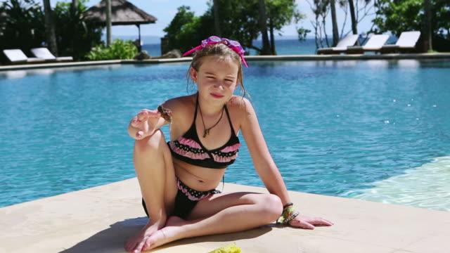 vídeos de stock e filmes b-roll de ms td shot of young girl sitting on edge of pool / ubud, bali, indonesia - só uma rapariga