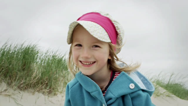 cu shot of young girl smiling at beach / st. peter ording, schleswig holstein, germany  - cap stock videos & royalty-free footage
