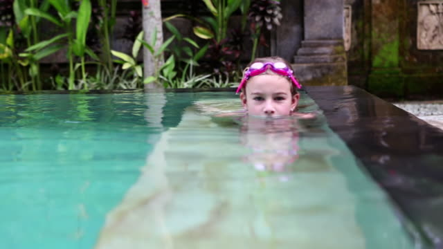 CU Shot of young girl swimming in outdoor pool / Ubud, Bali, Indonesia