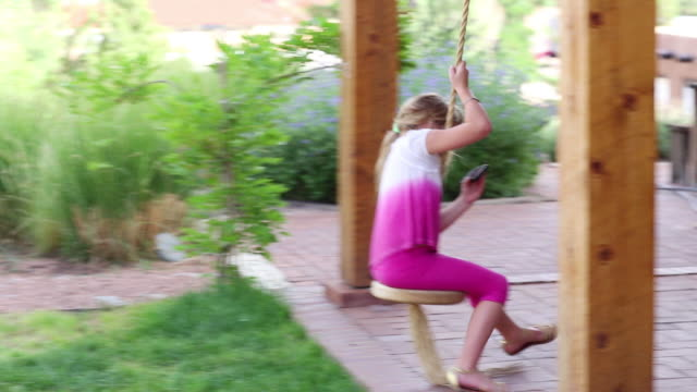MS TS Shot of young girl swinging and looking at her phone / Lamy, New Mexico, United States