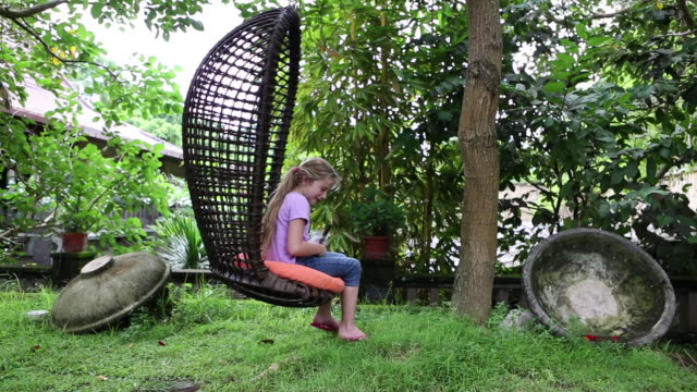 ms shot of young girl swinging in chair / ubud, bali, indonesia - slipper stock videos & royalty-free footage