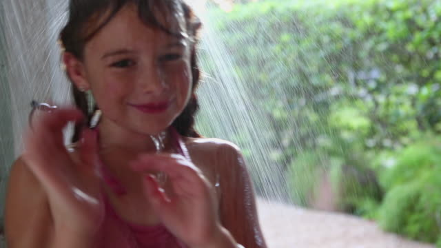 CU Shot of young girl taking outdoor shower / St. Simons Island, Georgia, United States