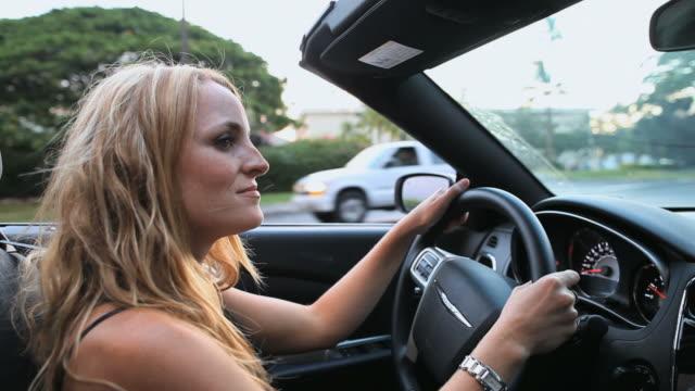 ms pov shot of young lady driving convertible down tree lined street at sunset in waikoloa beach resort / waikoloa village, hawaii, big island, united states - 腕時計点の映像素材/bロール