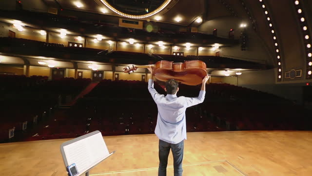 ws ts shot of young male cellist acknowledges an imaginary audience from the stage in an empty concert hall audio / ann arbor, michigan, united states - violin stock videos & royalty-free footage