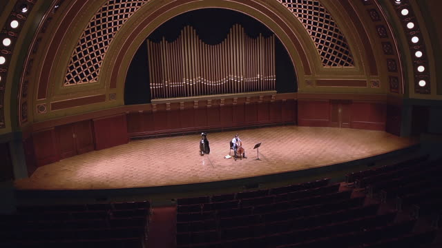 ws shot of young male cellist practicing solo piece on stage in empty concert hall audio / ann arbor, michigan, united states - adult stock videos & royalty-free footage