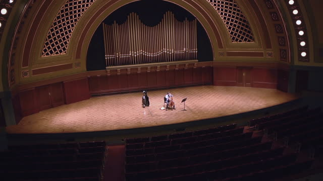 ws tu shot of young male cellist practicing solo piece on stage in empty concert hall audio / ann arbor, michigan, united states - concert hall stock videos and b-roll footage