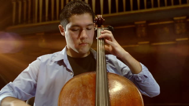 ms td shot of young male cellist practicing solo piece on stage in empty concert hall audio / ann arbor, michigan, united states - cellist stock videos & royalty-free footage