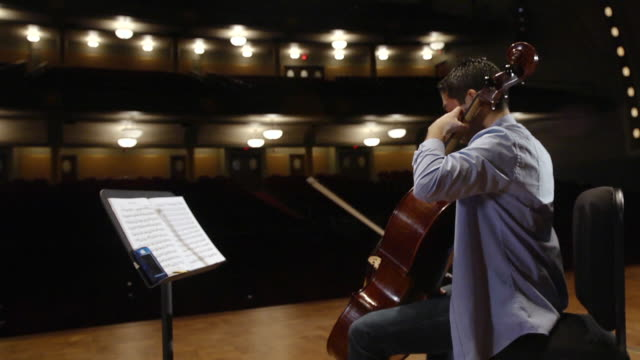 ms shot of young male cellist practicing solo piece on stage in empty concert hall audio / ann arbor, michigan, united states - concert hall stock videos & royalty-free footage