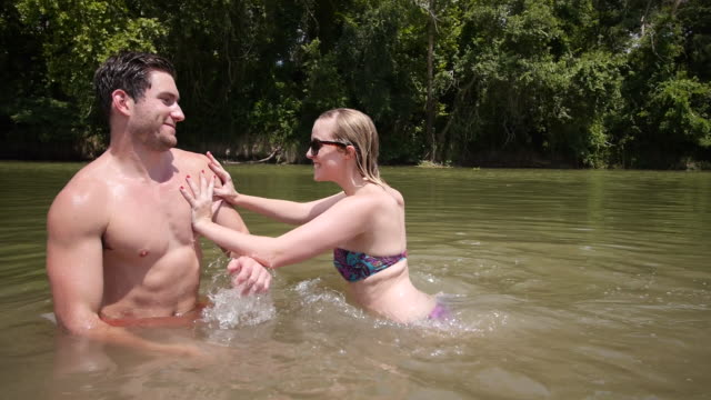 ms slo mo shot of young man and woman in lake having fun, woman pushes guy and swims away / austin, texas, united states - standing water stock videos and b-roll footage
