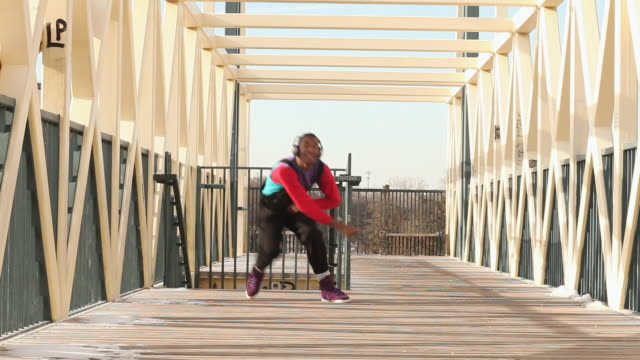 ms shot of young man dancing on bridge in urban area / minneapolis, minnesota, united states - bib overalls stock videos and b-roll footage