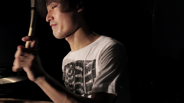 cu td pan shot of young man playing drums / shinjuku, tokyo, japan - パフォーマンス点の映像素材/bロール