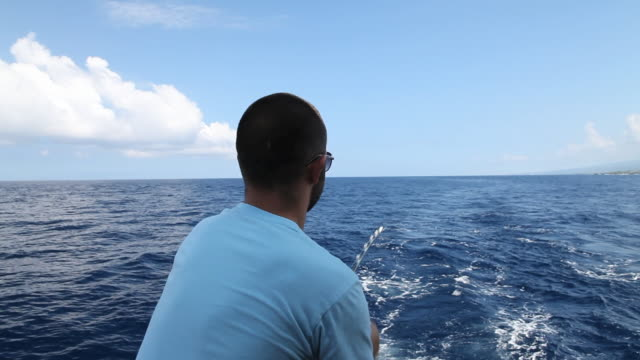 MS POV Shot of young man reeling in fishing line with ocean waves / Kealakekua, Hawaii, Big Island, United States