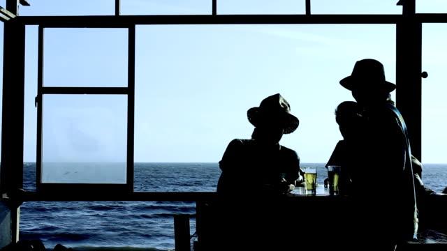 ms shot of young men enjoy talking and drinking at cafe by sea / shonan, kanagawa, japan - five people stock videos & royalty-free footage